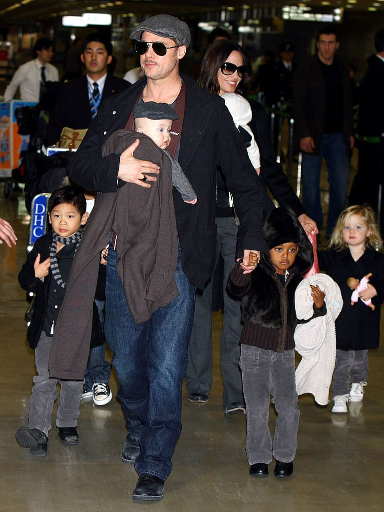 Pitt holding Knox in a baby carrier as he walked his other kids | Photo: Getty Images