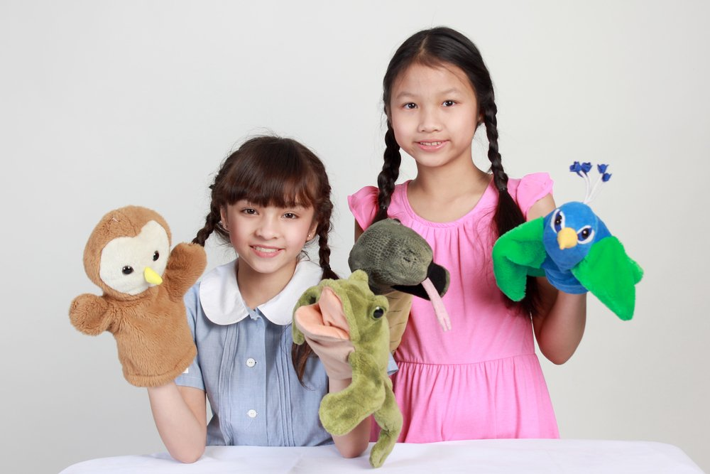 Two girls play puppet show | Photo: Shutterstock