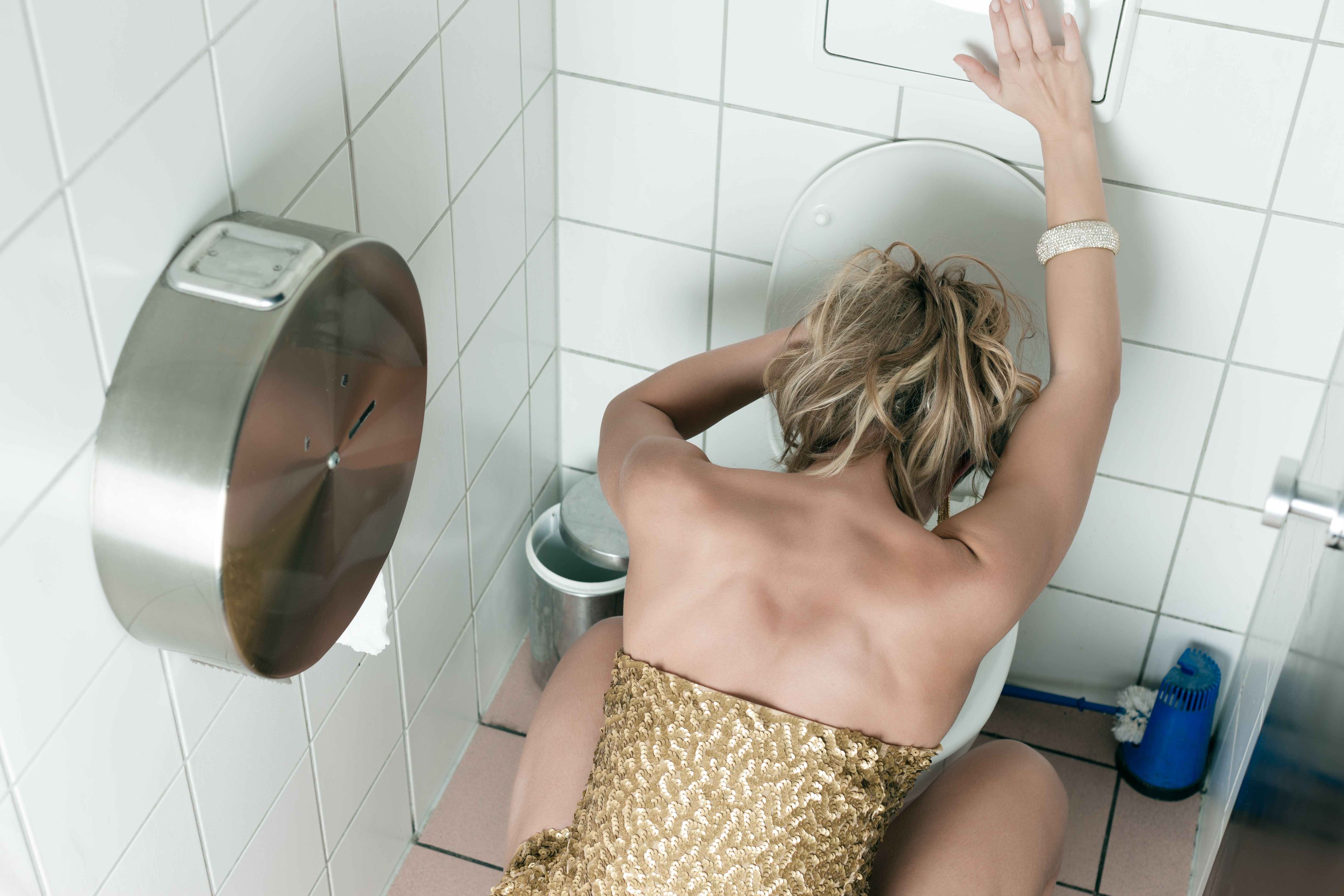 A sick woman throwing up in the bathroom. | Source: Shutterstock