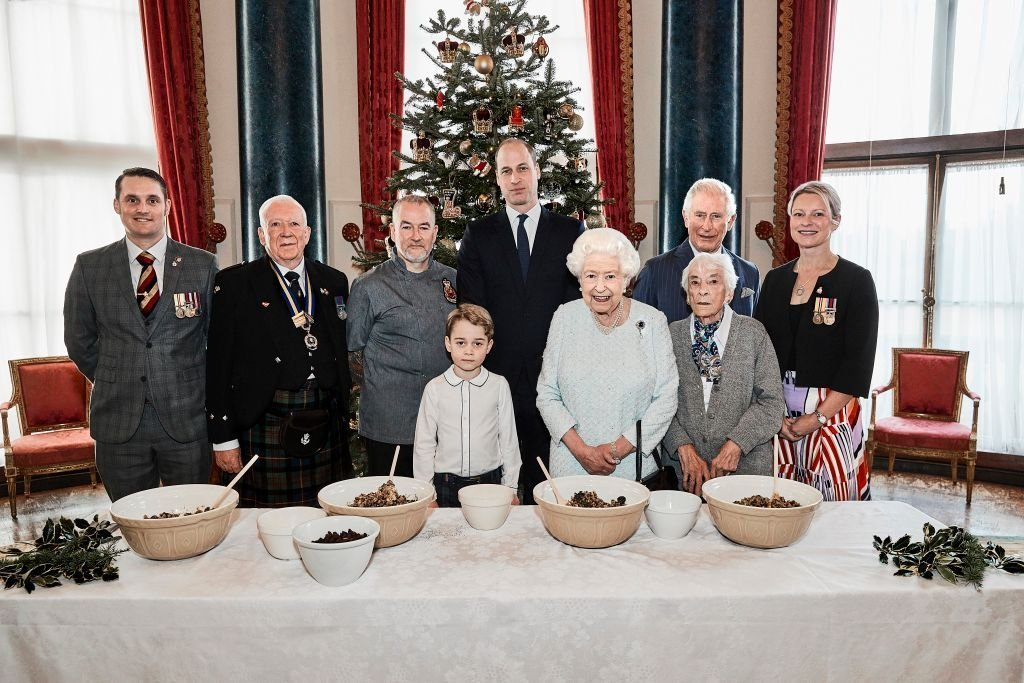 Veterans pose alongside Prince George, Prince William, Duke of Cambridge, Queen Elizabeth II and Prince Charles, Prince of Wales in the Music Room at Buckingham Palace, as part of the launch of The Royal British Legion's Together at Christmas initiative. | Photo: Getty Images
