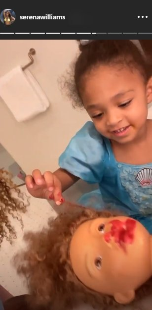 Alexis Olympia in a photo making over her doll Qai Qai's face. | Photo: Instagram/Serenawilliams