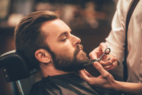 A young man having his beard trimmed. | Source: Shutterstock.