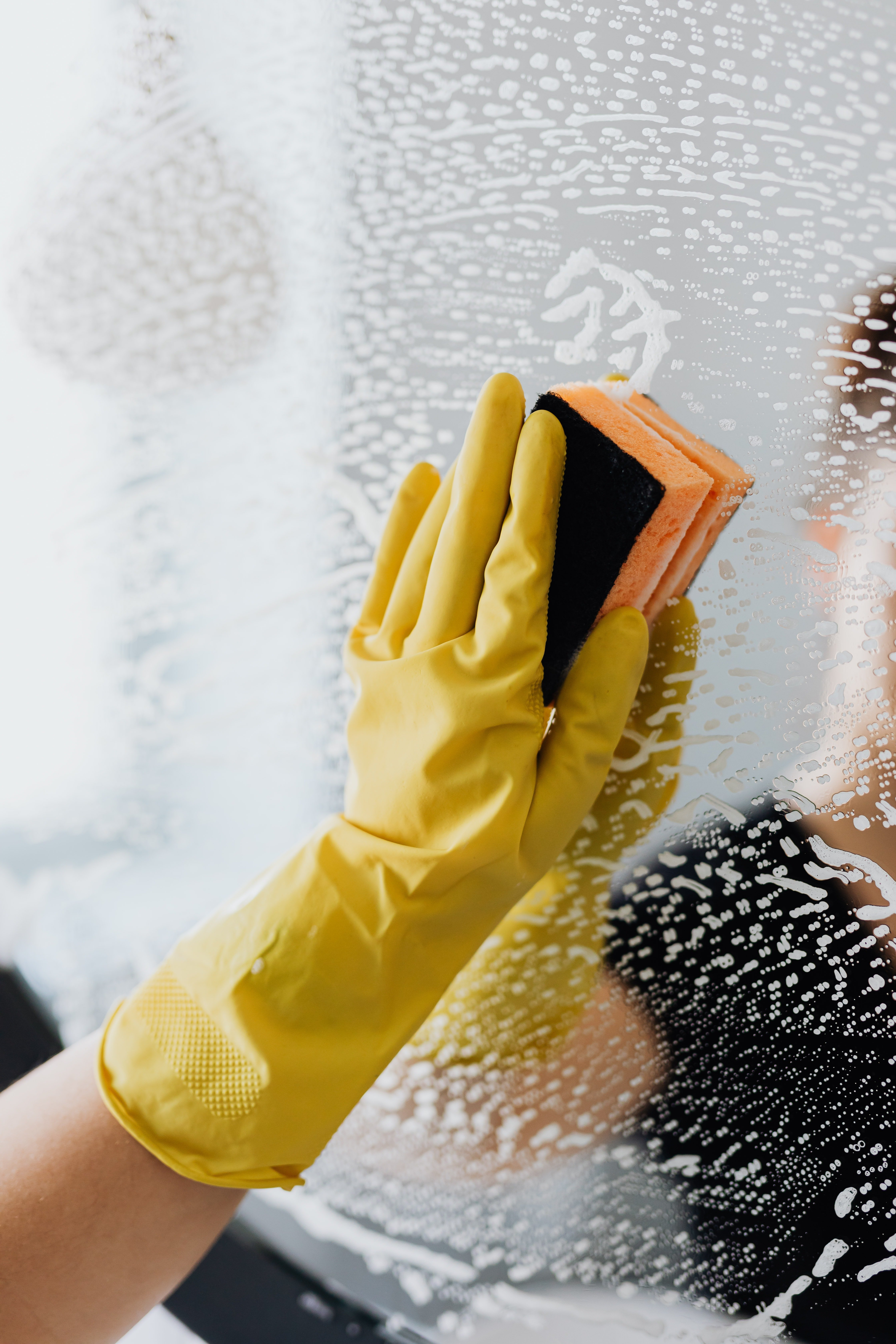 A person cleaning the mirror with a sponge | Photo: Pexels