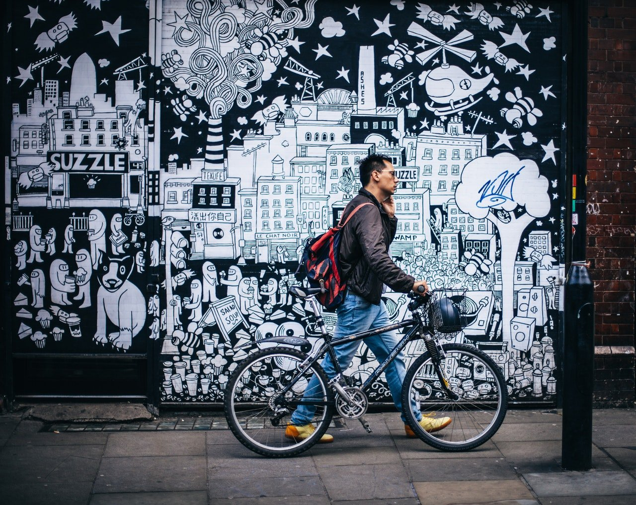 Photo of young man pushing his bicycle in the city. | Source: Pexels/Clem Onojeghuo