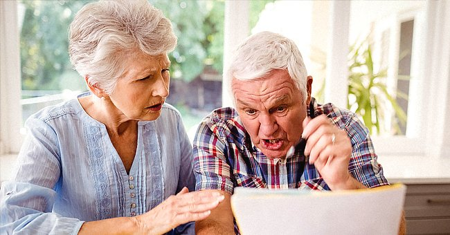 An elderly couple looking at a document. | Source: Shutterstock