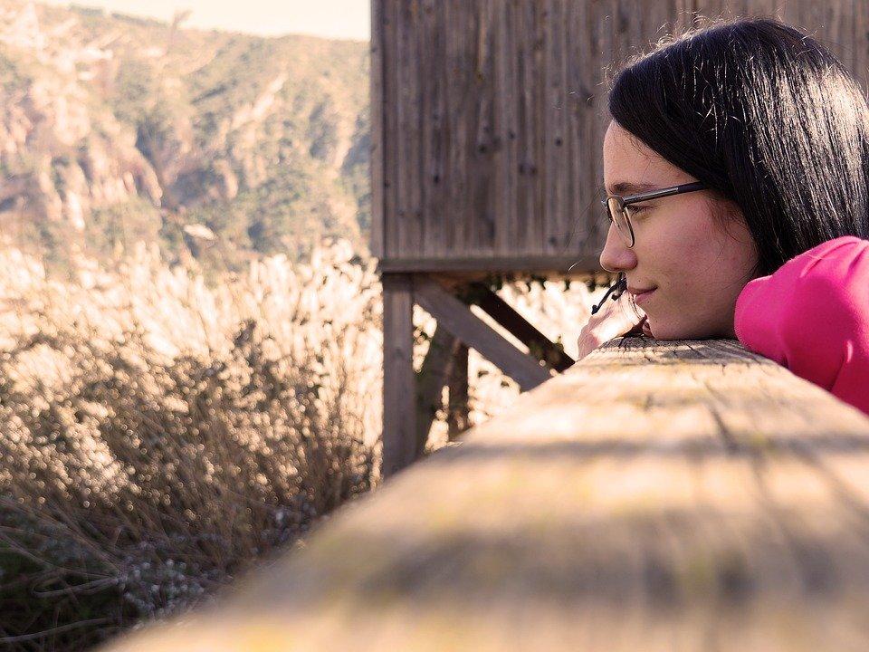 Mujer pensativa con su quijada posada sobre un tabón de madera. | Imagen: Pixabay