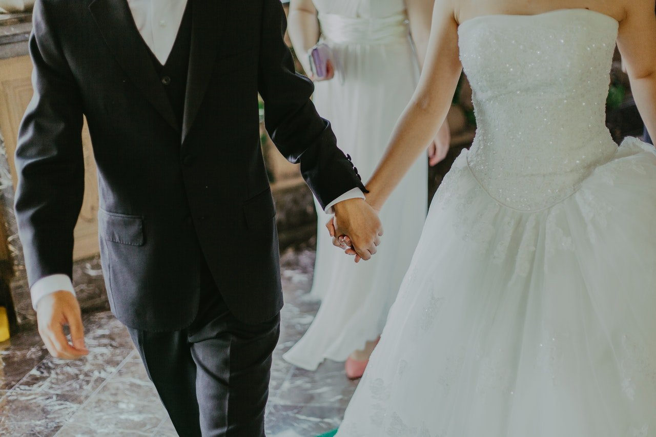 Groom and bride holding hands at a wedding. | Source: Pexels/Jeremy Wong
