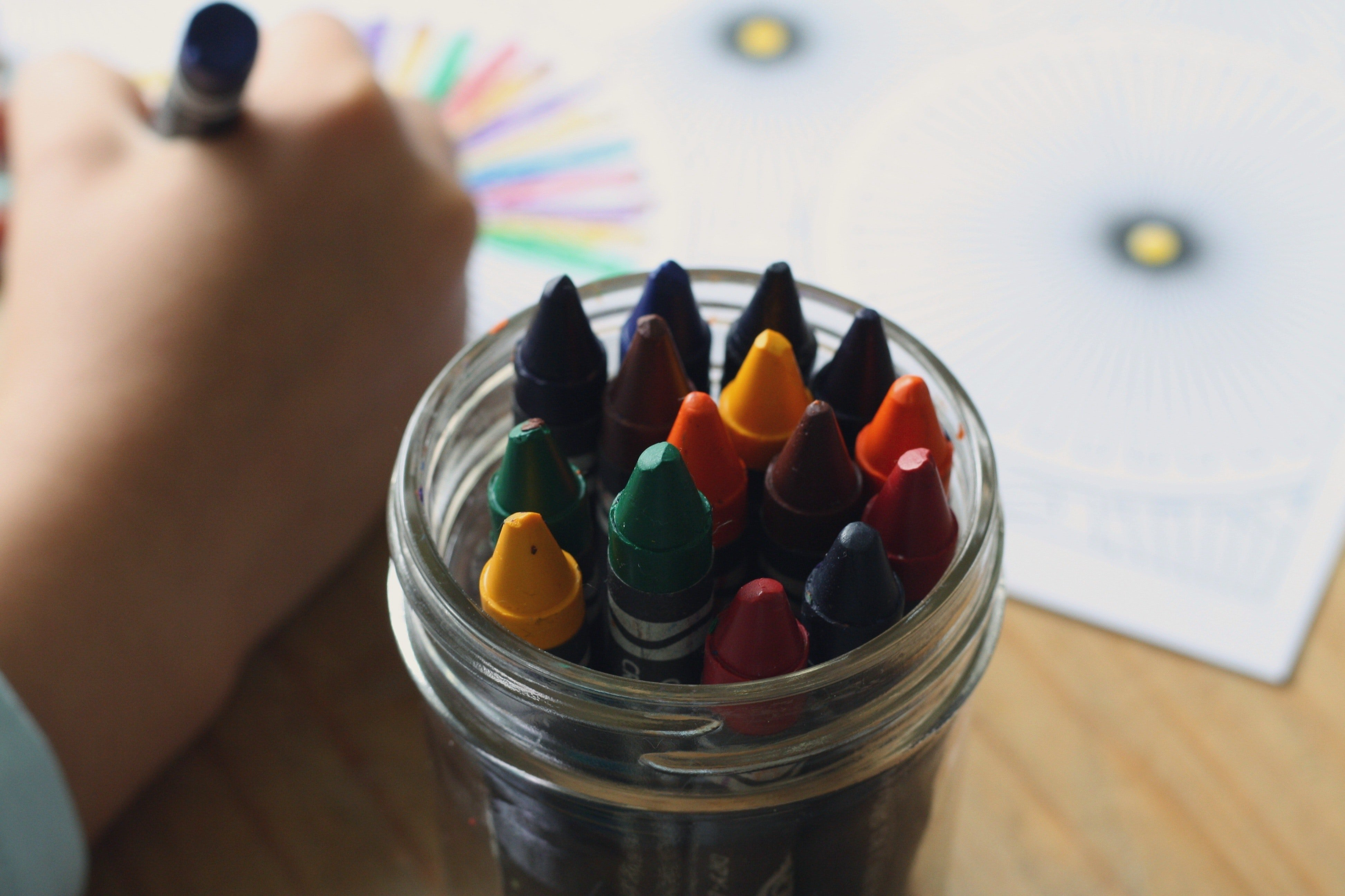 Child drawing with crayons. | Source: Pexels