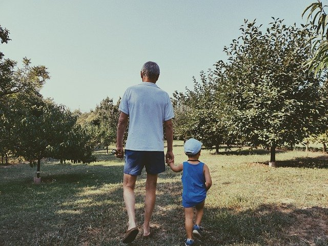 Old man walks through orchard with young boy | Photo: Pixabay
