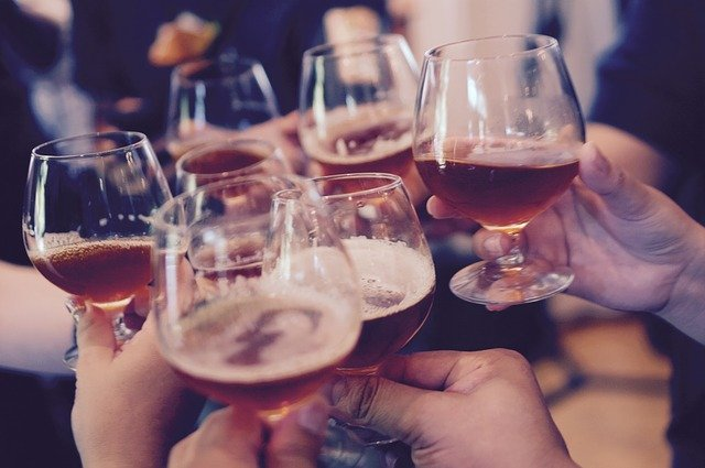 Persons holding up filled glasses | Photo: Pixabay