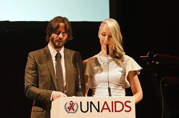 Keanu Reeves (L) and Alexandra Grant speak at the UNAIDS Gala during Art Basel 2016 at Design Miami/ Basel in Basel | Photo: Getty Images