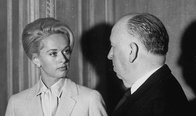 """Alfred Hitchcock and Tippi Hedren with a bird on the hand in the Cannes film festival, on the occasion of the presentation of the movie """"""""birds""""""""1963.   Source: Getty Images"""
