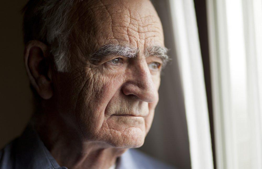 Un homme âgé regardant par la fenêtre. | Photo : Shutterstock