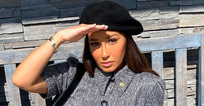 Adrienne Bailon Braves the Snow as She Exposes Toned Legs in a White T-Shirt Dress & Sweater