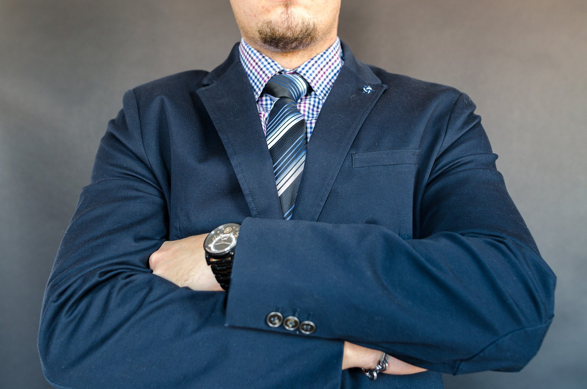A close-up of a man in a suit with his hands folded against his chest   Photo: Pixabay/Goumbik