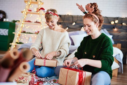 Sisters Opening Christmas Presents While Sitting At Home | Photo: Getty Images