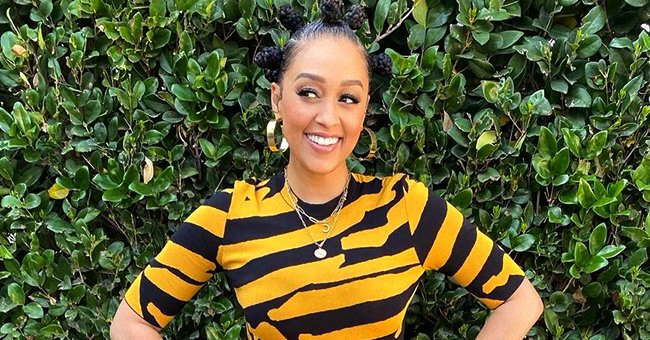 Tia Mowry Sports Bantu Knots Showing Hourglass Figure in a Yellow & Black Top with Tight Pants