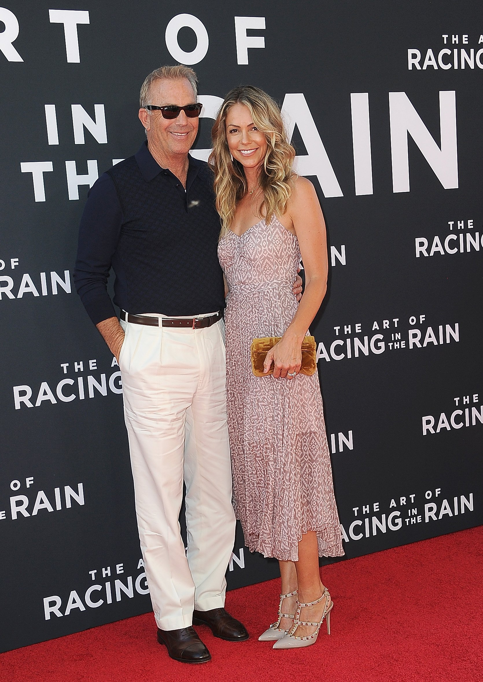 """Kevin Costner and Christine Baumgartner arrive for the Premiere of """"The Art Of Racing In The Rain""""  on August 1, 2019, in Los Angeles, California. 