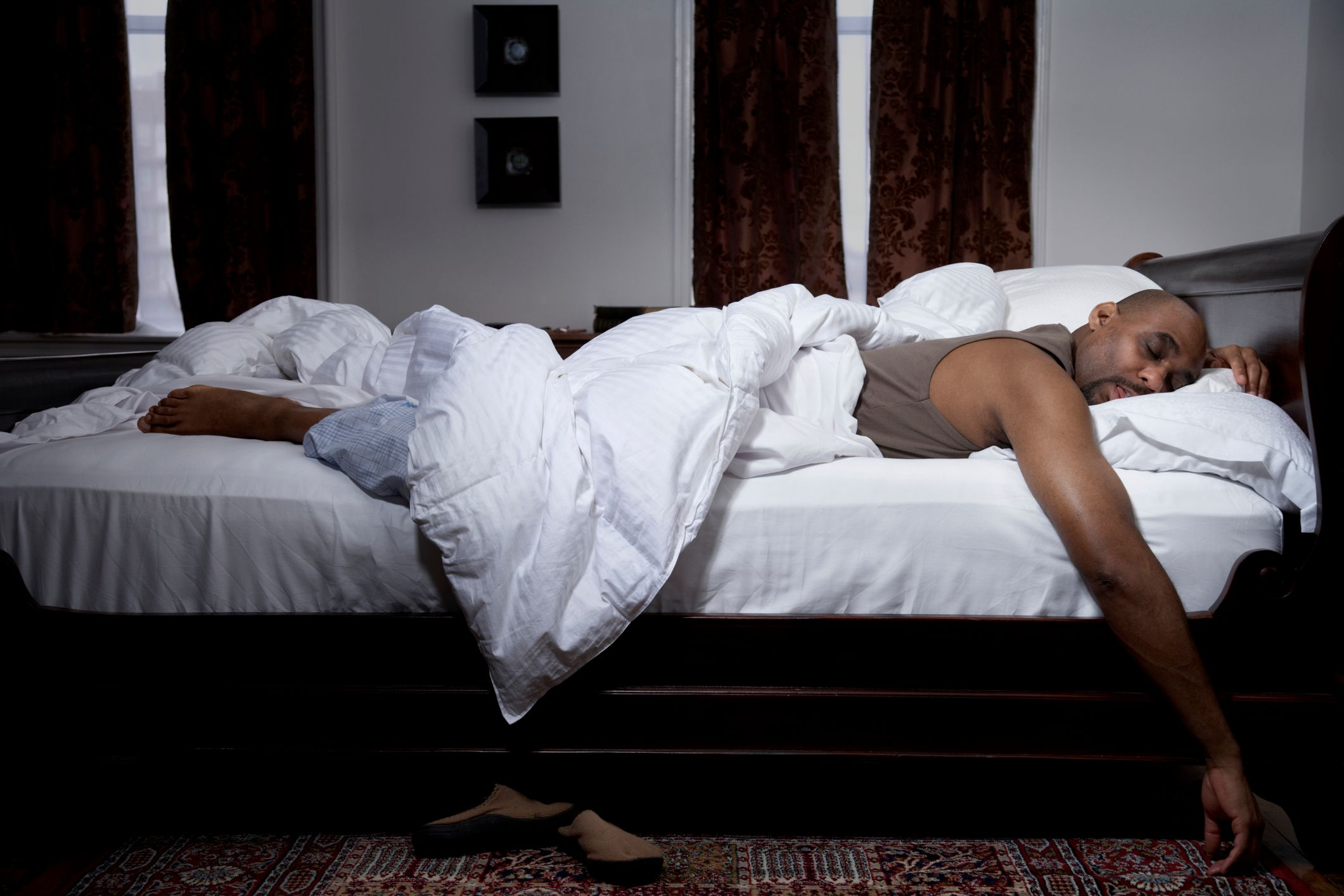 A man sleeping comfortably on a bed.   Photo: Shutterstock