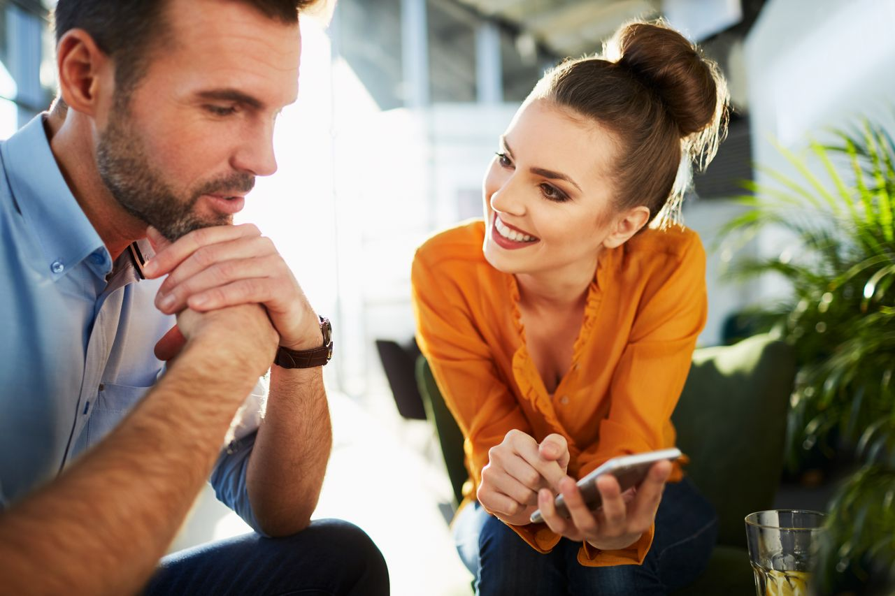 A man and woman talking in an office. | Source: Shutterstock