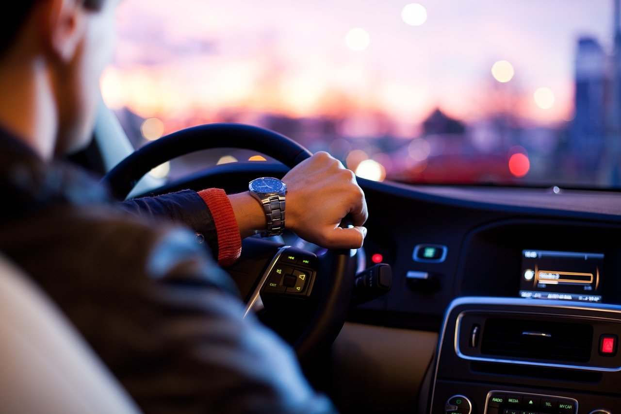 A man driving a car with one hand on the steering wheel   Photo: Pixabay/Free-Photos