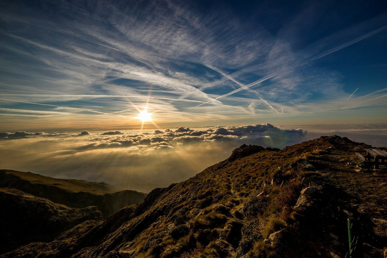 A mountainous landscape with the sun rising amongst the clouds   Photo: Pixabay/Dan Fador