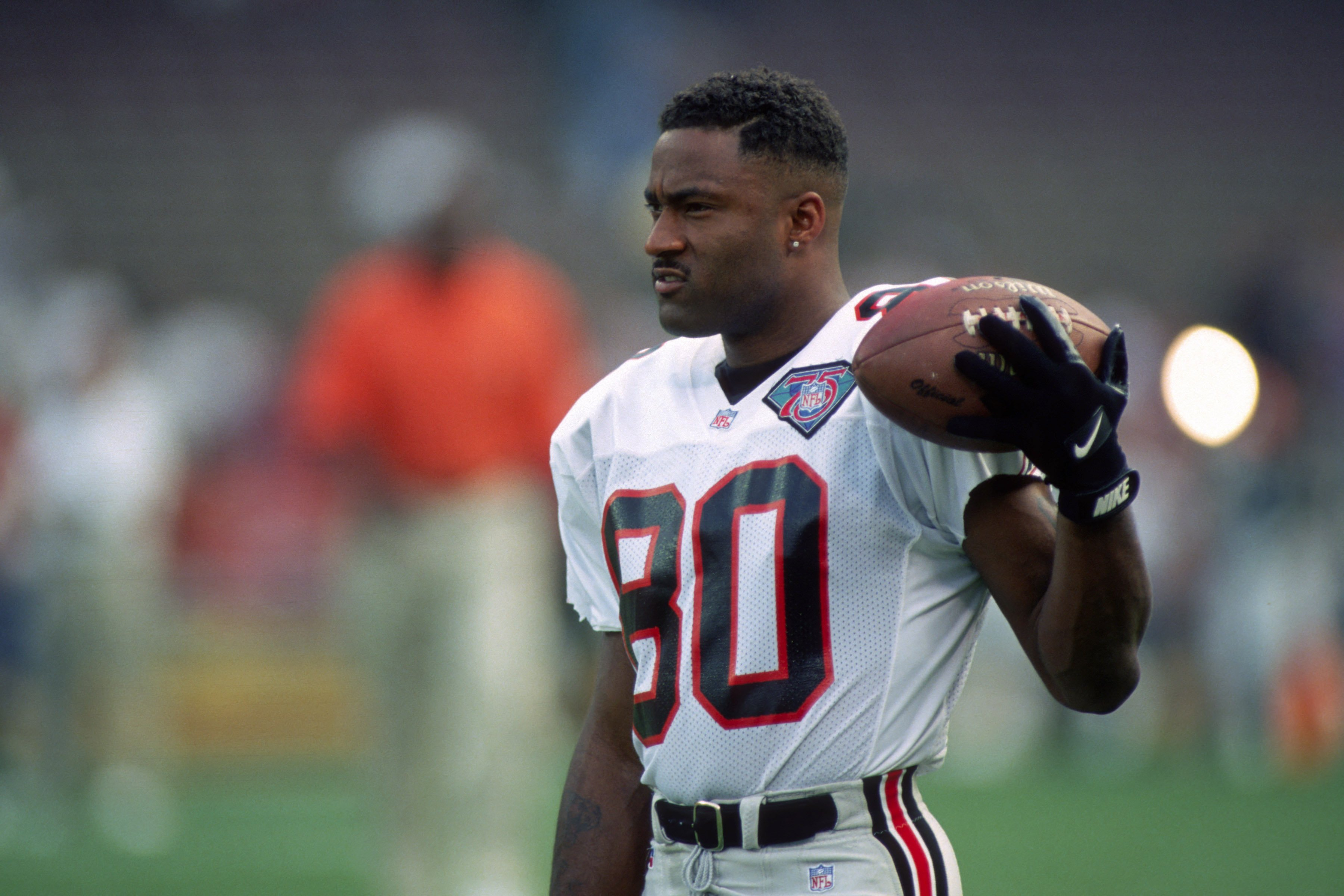 Andre Rison #80 of the Atlanta Falcons looks on from the field during pregame warmup prior to a preseason game against the Cleveland Browns at Cleveland Browns Stadium on August 19, 1994| Photo: Getty Images