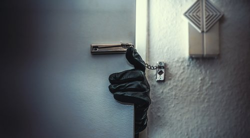 A burglar breaking into a home. | Source: Shutterstock.