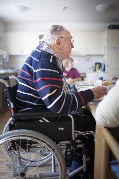 An old man sitting in his wheelchair eating lunch at a nursing home on the island of Borkum | Photo: Getty Images