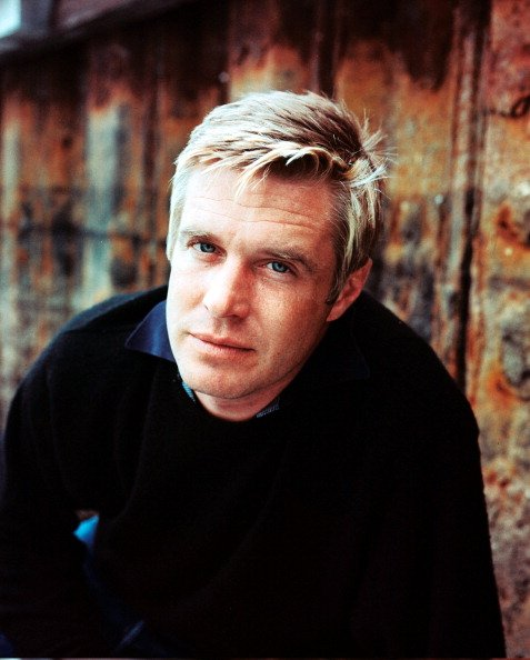 George Peppard prend la pose dans son jumper noir par devant un mur a la surface rugueuse.. | Getty Images