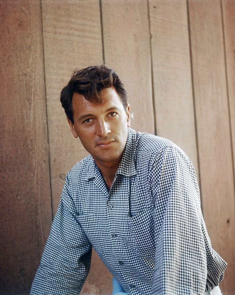 A portrait of Rock Hudson against a wooden backdrop on 01 January, 1960 | Photo: Getty Images