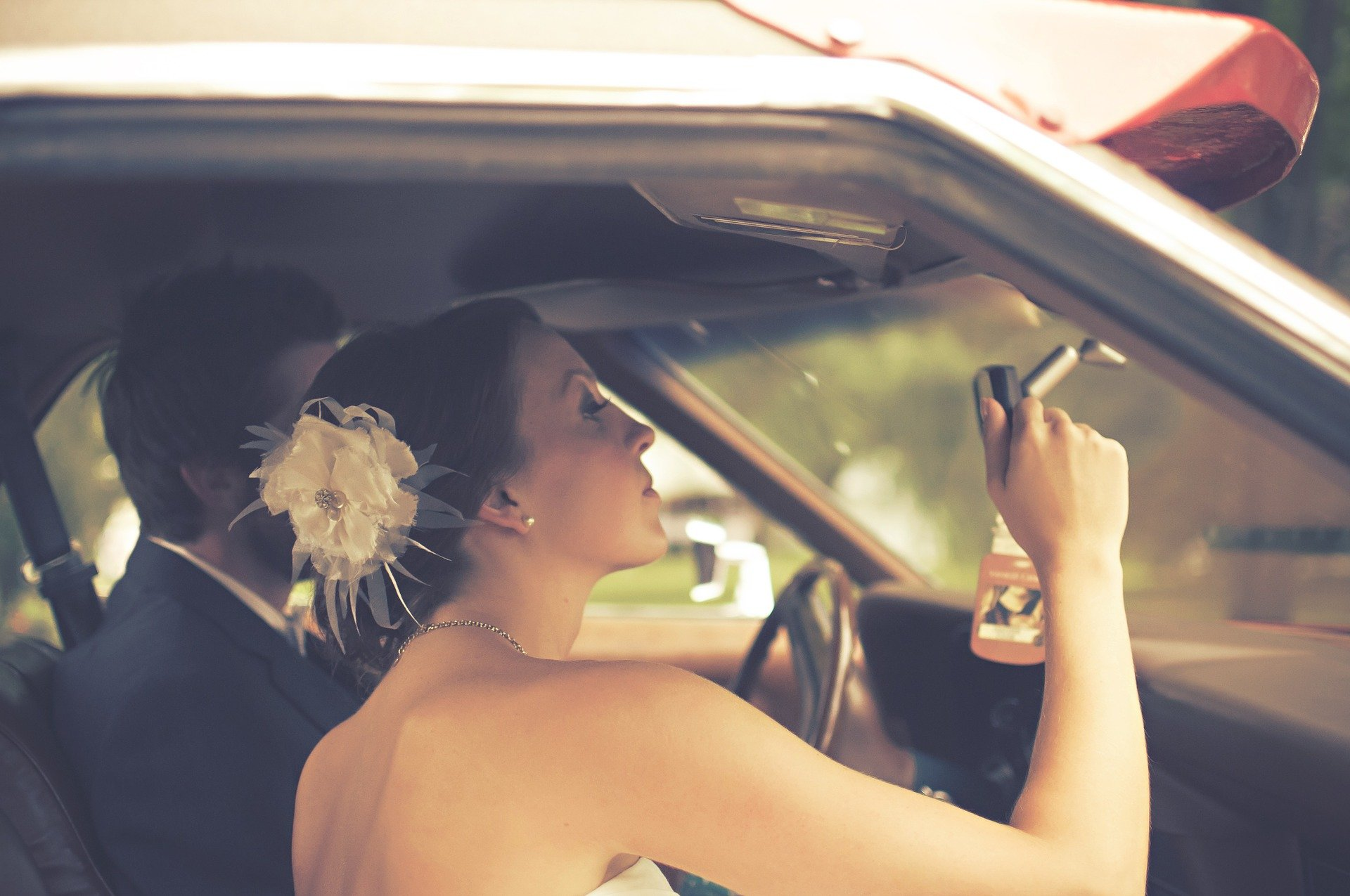 A couple sitting in a car while the woman looks at herself in the rearview mirror   Photo: Pixabay/Scott Webb