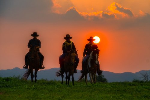 Three cowboys riding with the sunset behind them. | Source: Shutterstock.