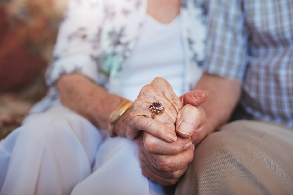 Cropped shot of elderly couple holding hands while sitting together at home. | Photo: Shutterstock
