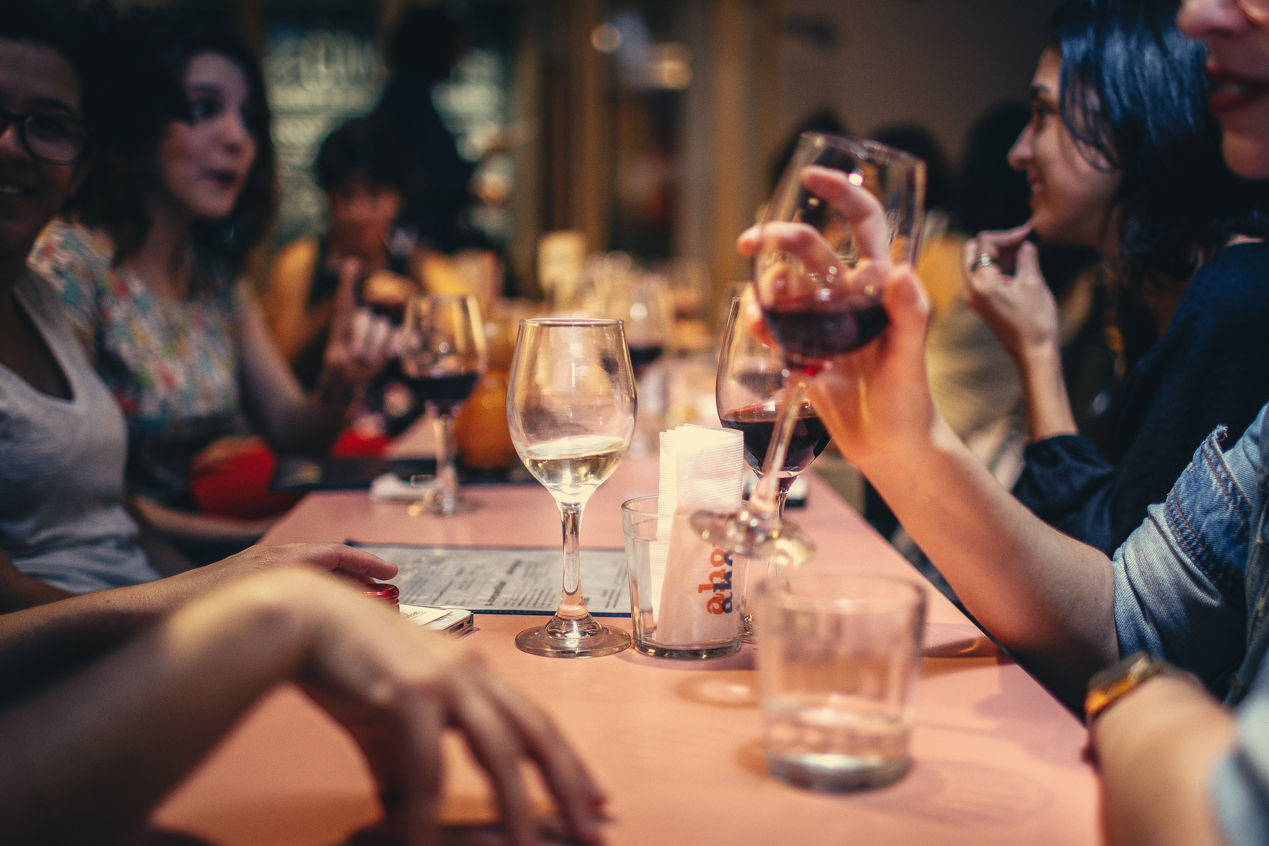 A table full of people and drinks.   Pexels/ Helena Lopes