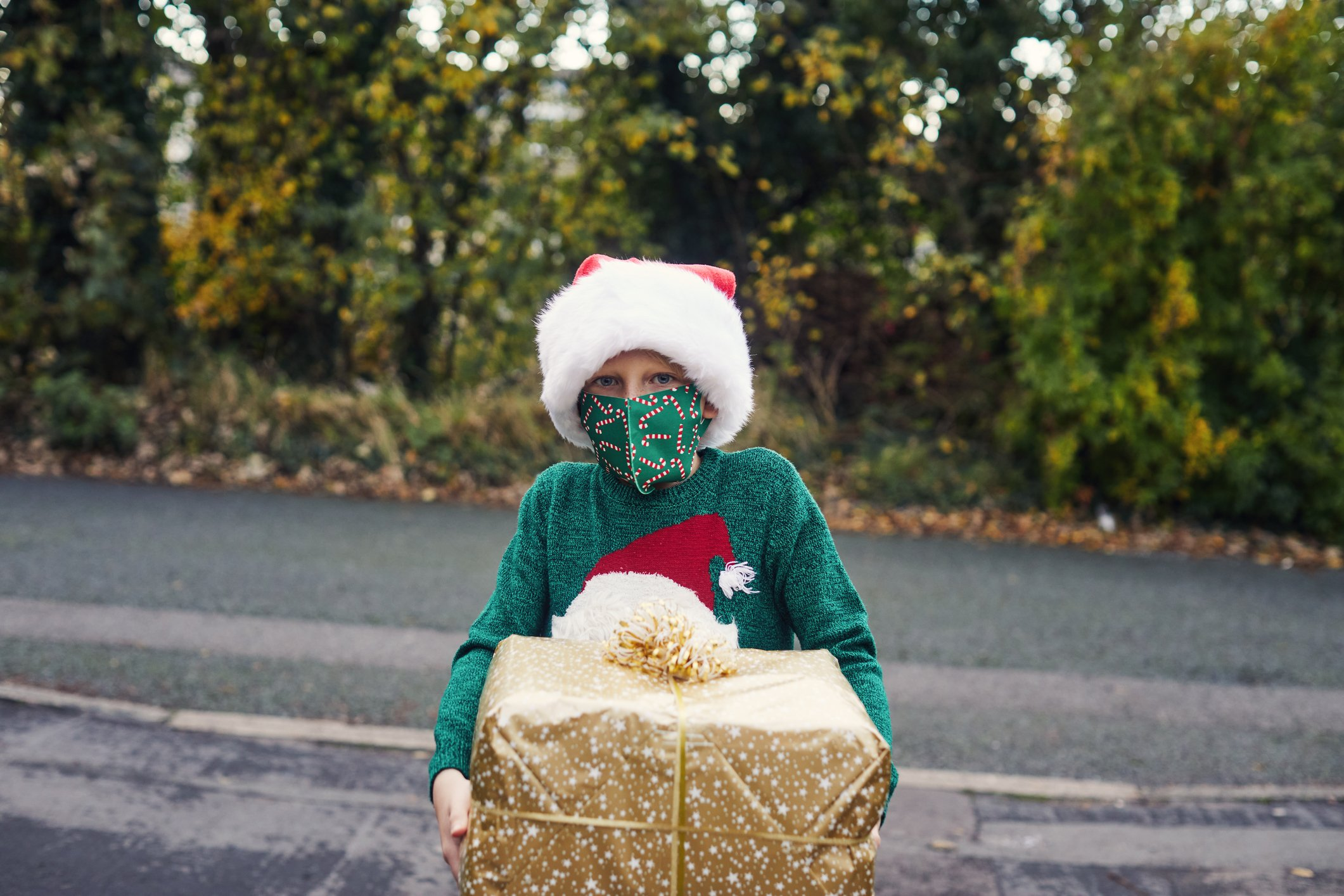 A boy on a Christmas hat and a facemask holding a Christmas present. | Photo: Getty Images