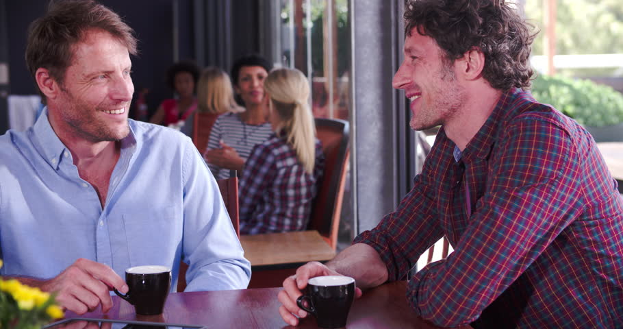Two mature mature male friends sitting, and talking over coffee | Photo: Shutterstock