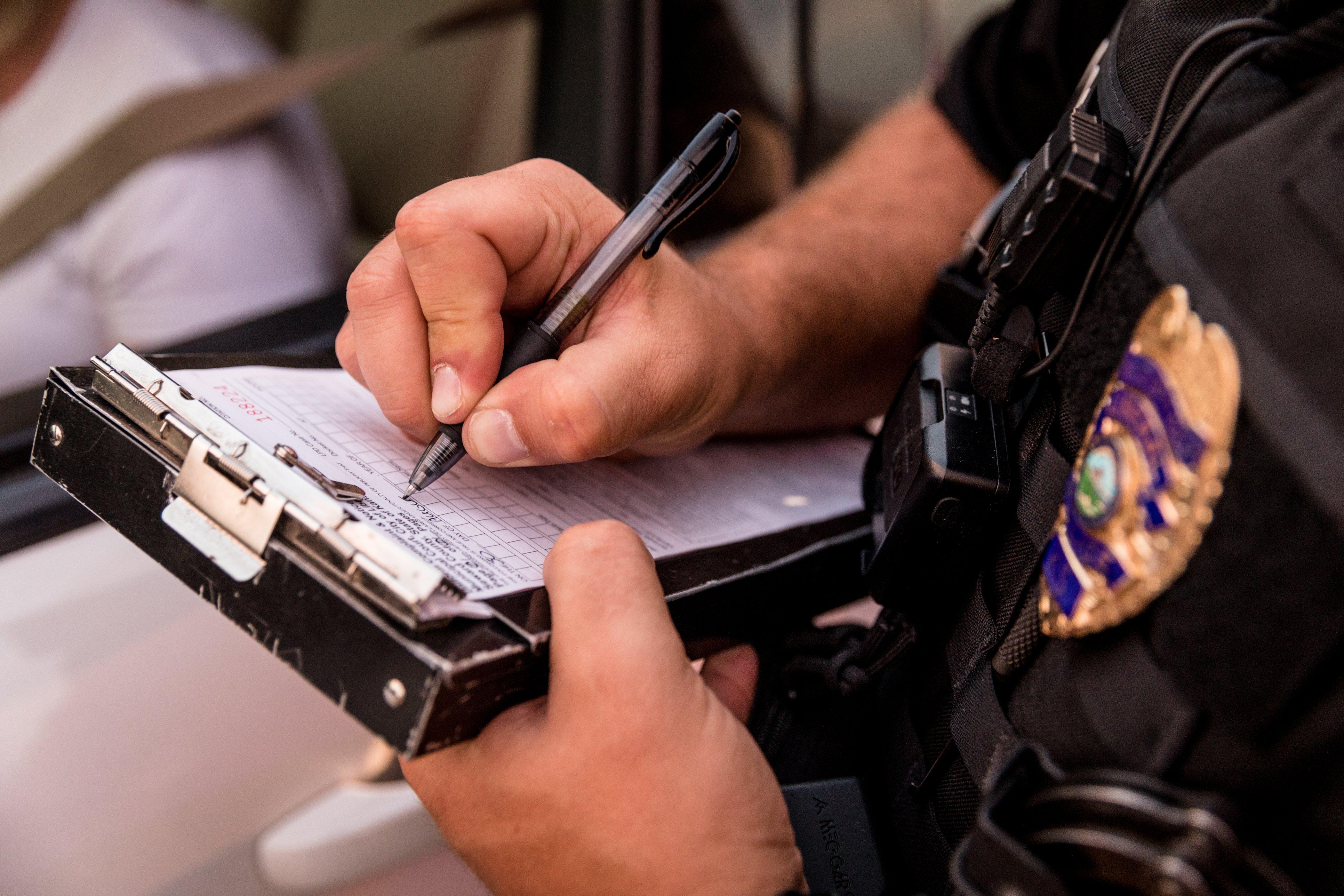 Polizeibeamte schreibt ein Ticket   Quelle: Shutterstock