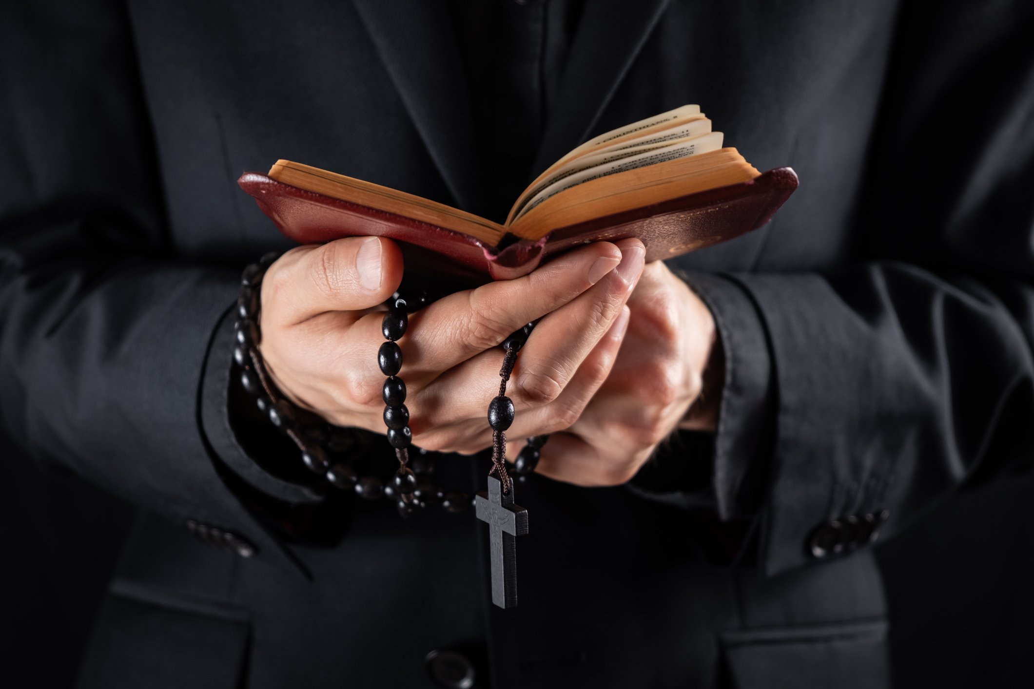 Hands of a christian priest dressed in black holding a crucifix and reading New Testament book | Photo: Getty Images