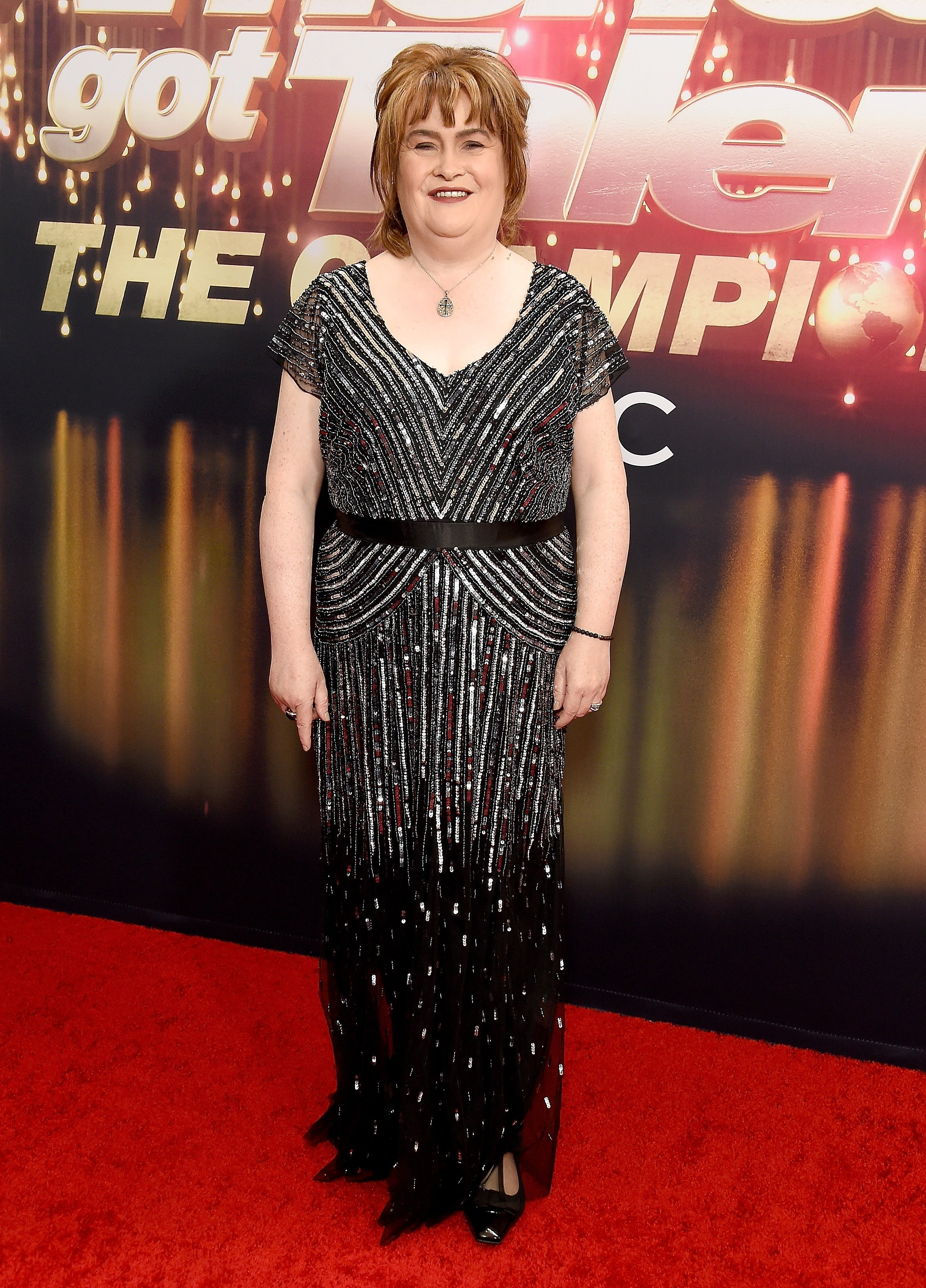 Susan Boyle posing in front of the show's banner | Photo: Getty Images