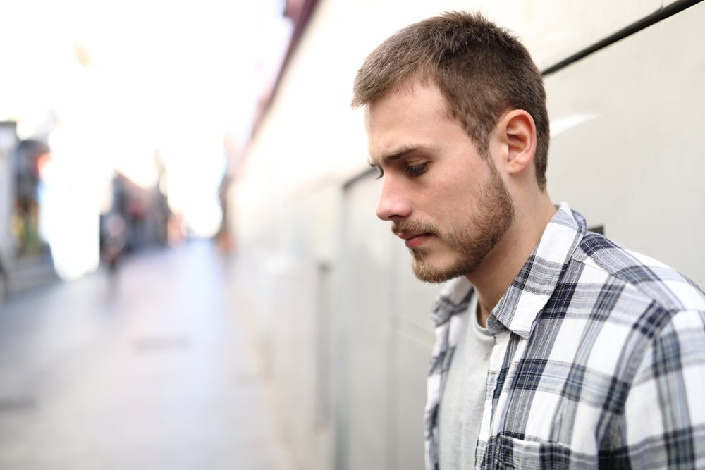 A side view portrait of a sad man standing in the street   Photo: Shutterstock/Antonio Guillem