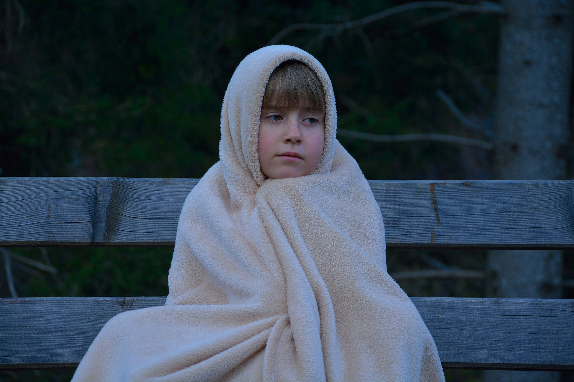 A child wearing a blanket sitting on top of a bench | Source: Pixabay