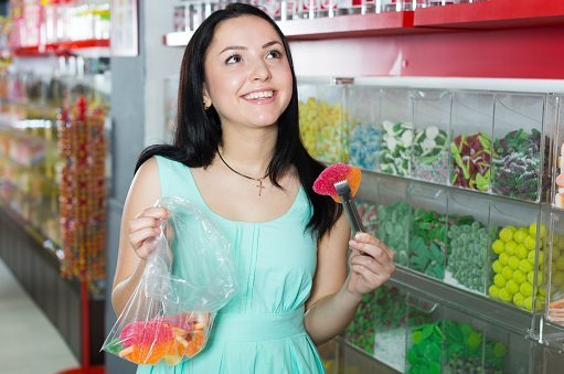 Photo of a young girl in a sweets store picking up candies | Photo: Getty Images