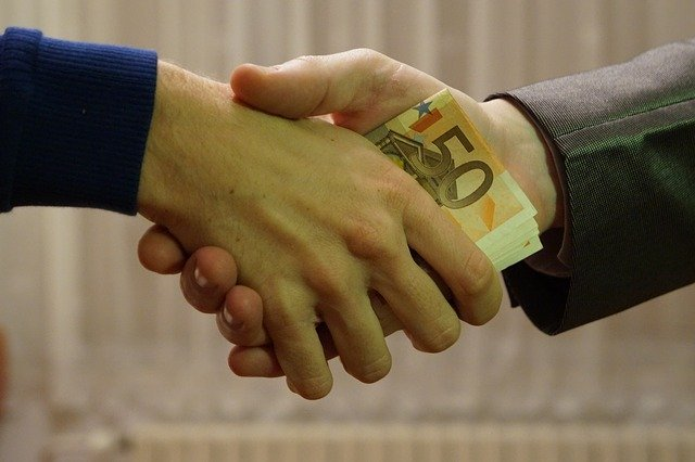 Two men shake hands with money in their hands   Photo: Pixabay