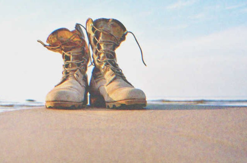 Pair of military boots on the beach |Source: Shutterstock