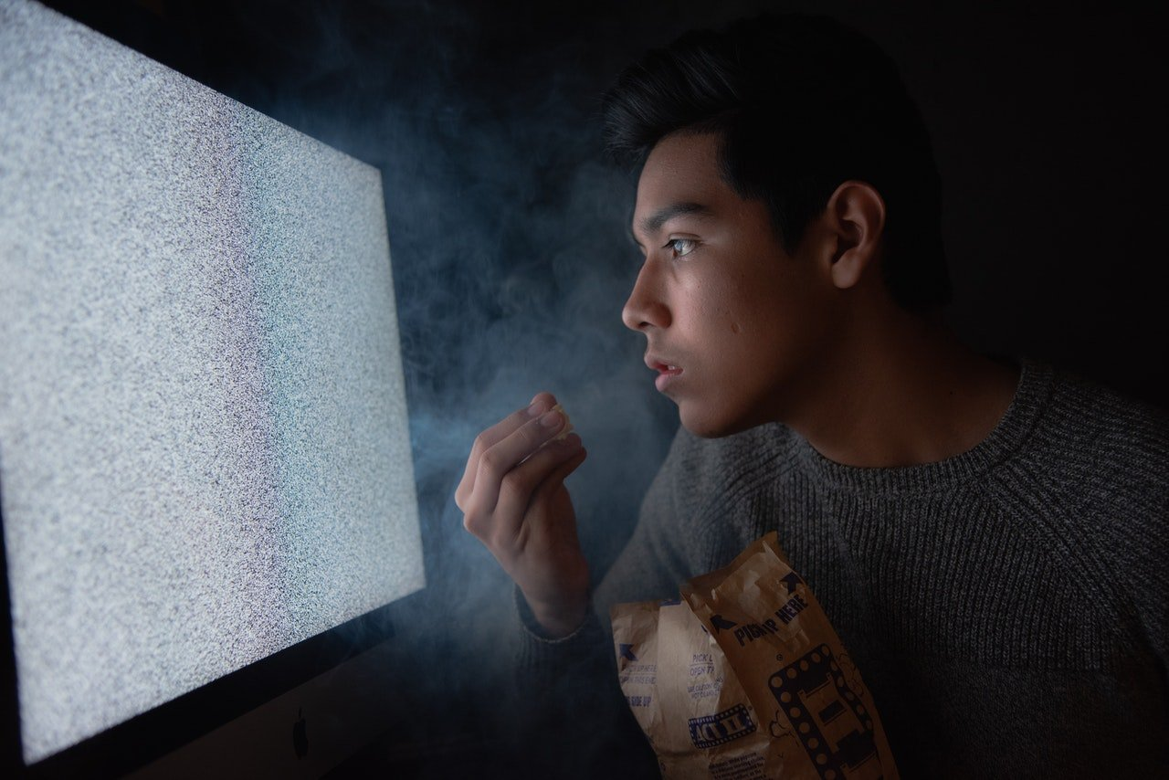 Man eating chips while watching TV| Photo Amateur Hub from Pexels