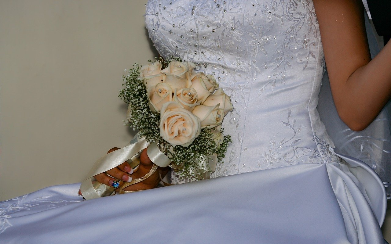 A woman wearing a wedding dress and holding a bouquet of white roses. | Image: Pixabay.