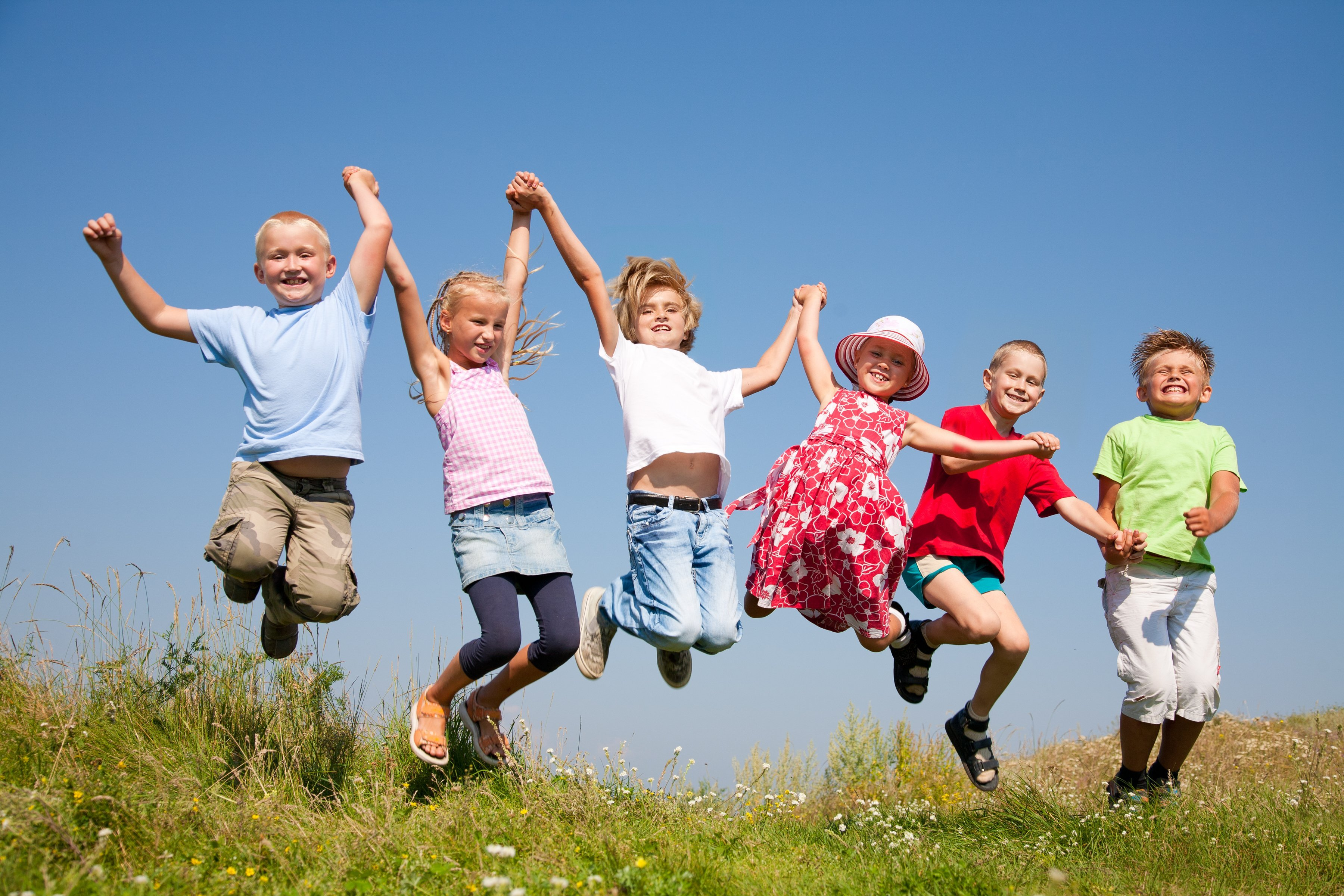 Group happy children jumping on summer meadow against blue sky | Photo: Shutterstock.com