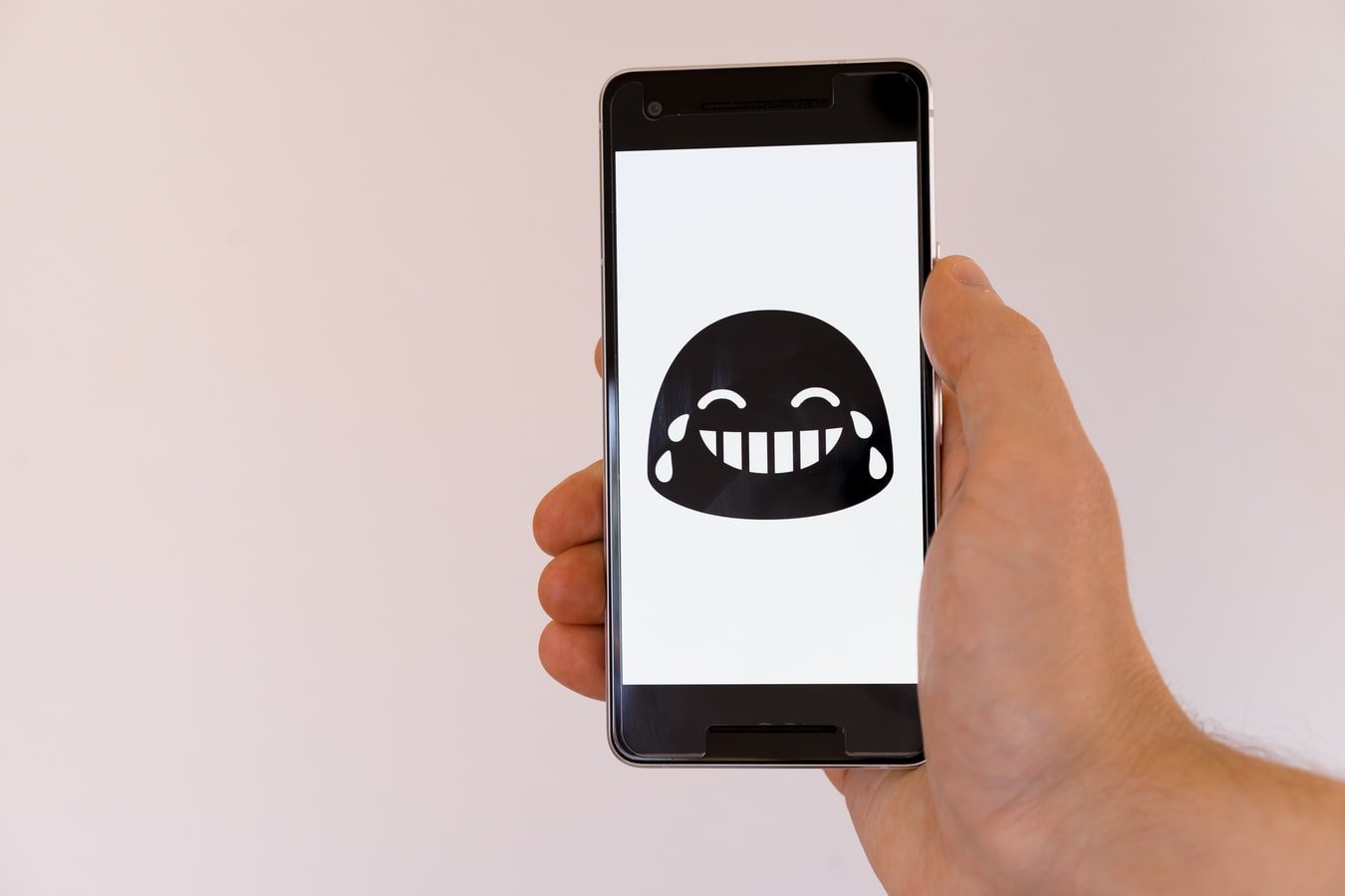 A laughing out loud emoji on a cell phone.   Photo: Unsplash/Markus Winkler