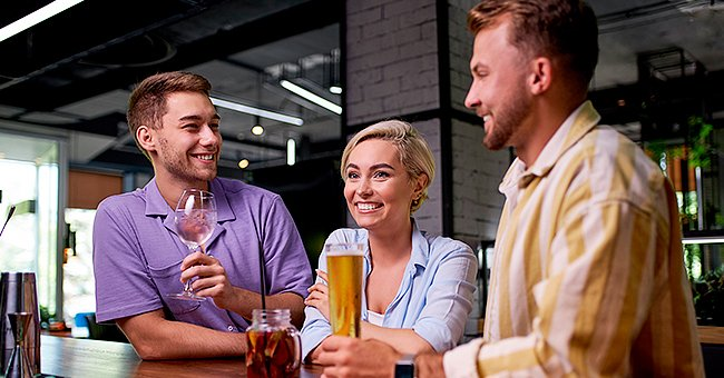 Two friends were sitting in their bar when a gorgeous young woman entered the bar. | Photo: Shutterstock